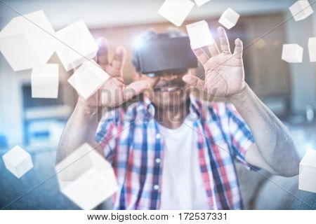 Digitally generated grey cubes floating against senior man wearing virtual reality headset in living room 3d