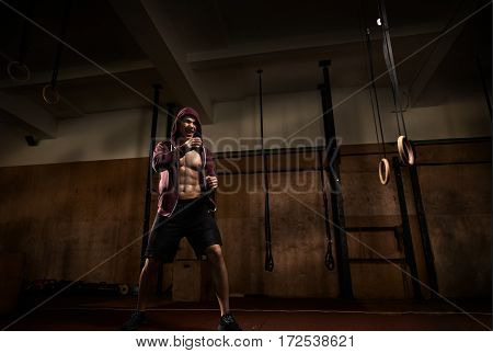 Young muscular male fighter practicing kicks in the gym