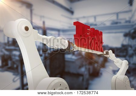Computer graphic image of robotic hand holding team work text against defocused image of machinery