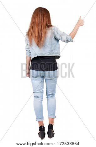 Back view of  woman thumbs up. Rear view people collection. backside view of person. Isolated over white background. slender redhead in a jeans shows the symbol of success or hitchhiking