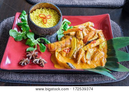 Thai cuisine, traditional vegetable mix with curry sauce and rice in a cocos bowl, basilic leaves, red plate, asian food