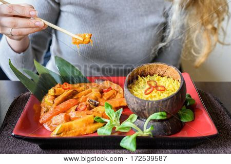 Woman with blonde hair eating with chopsticks traditional vegetable mix with curry sauce and rice in a cocos bowl, basilic leaves, red plate, asian food. Silver sweater, marriage ring
