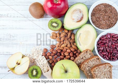 Avocado flax seeds whole grain bread kiwi nuts oatmeal beans and apples on wooden boards. Healthy food. Top view