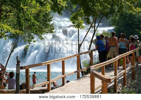 Tourists Walking In Front Of The Waterfalls Of The Krka
