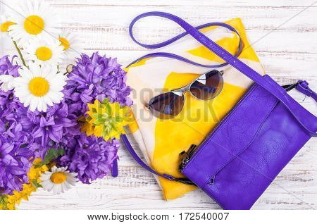 Womans accessories background with handbags neckerchief sunglasses and flowers. Summer womans outfits. Top view
