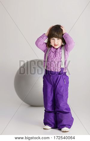 little cute girl in purple clothes holding his head and large ball for fitness on  gray background.
