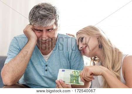 Sad husband give 100 euros to gold-digger young wife
