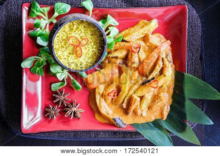 Thai cuisine, traditional vegetable mix with curry sauce and rice in a cocos bowl, basilic leaves, red plate, asian food, top view