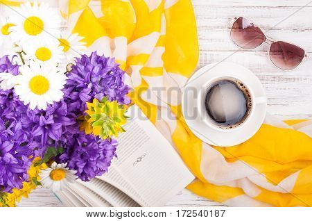 Cup of coffee book bouquet of flowers womans accessories sunglasses and neckerchief on wooden background. Summer rest concept background. Top view
