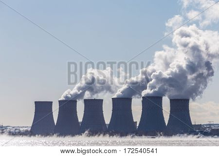 Cooling towers of a Nuclear energy station  or NPP with thick smoke on blue sky background. Copy space for text