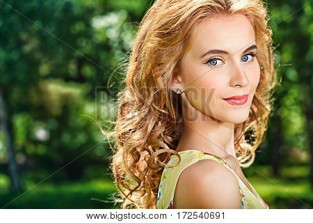Happy romantic girl in the park on a sunny summer day. Smiling young woman outdoor. Holiday, vacation.