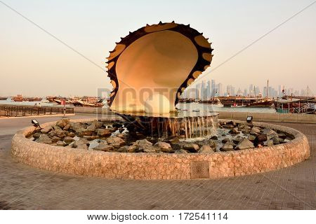 Doha, Qatar - November 2, 2016. Pearl monument in Doha, with people, cars, boats and buildings in the background, at dawn