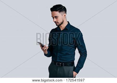 Sending important business messages. Serious young man in shirt typing text message using his smart phone while standing against grey background