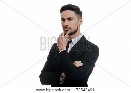 Lost in thoughts. Handsome young man in full suit holding hand on chin and looking away while standing against white background