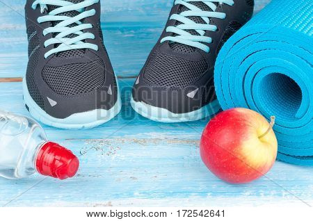 Sport equipment. Yoga mat sport shoes apple bottle of water on blue wooden background. Concept healthy lifestyle healthy food sport and diet