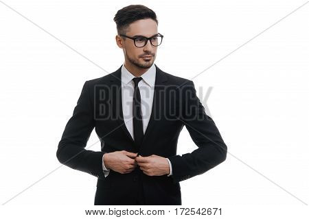 Looking just perfect. Handsome young man in full suit buttoning his jacket and looking away while standing against white background