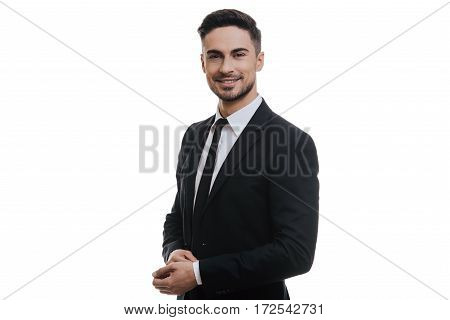 Young and successful. Handsome young man in full suit adjusting his sleeve and looking at camera while standing against white background