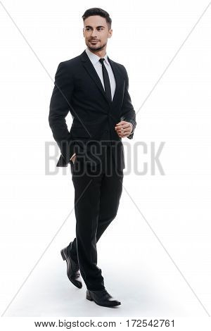 Perfect style. Full length of handsome young man in full suit holding one hand in pocket and looking away while standing against white background