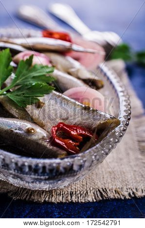 Small fish in brine with spices. Selective focus.