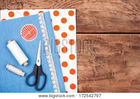 Sewing background. Fabric for sewing lace and accessories for needlework on old wooden table. Spool of thread scissors buttons sewing supplies. Set for needlework top view