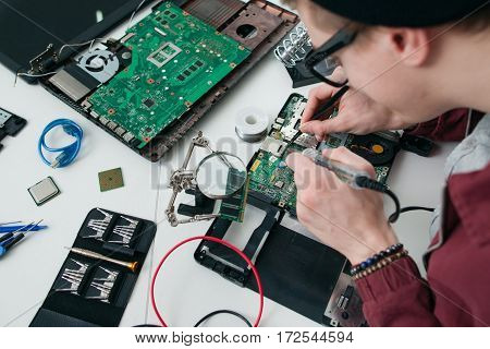 Repairman soldering electronic components on cpu. Young man fixing broken computer motherboard. Repair workshop, electronics development, business concept