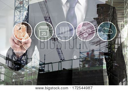 Crane and building construction site against midsection of businessman touching icon interface