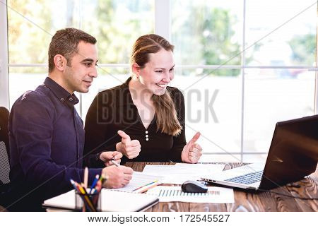Young And Confident Business People Working At Table In Office