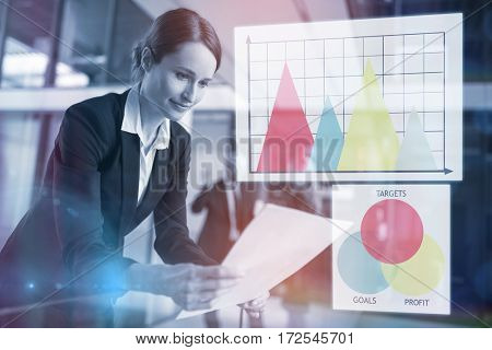 Graph against businesswoman standing in corridor reading document in office
