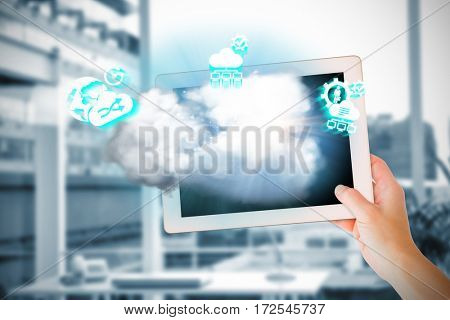 Masculine hand holding tablet against working desk in a office