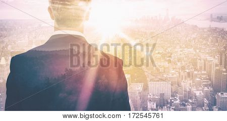 Rear view of an elegant businessman against sunrise over mountains