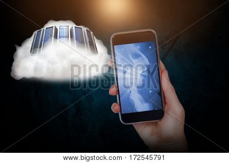 Hand holding mobile phone against against dark background