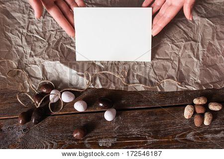 Hands with blank card on kitchen table flat lay. Top view on woman holding empty paper and preparing sweet package for holiday, free space