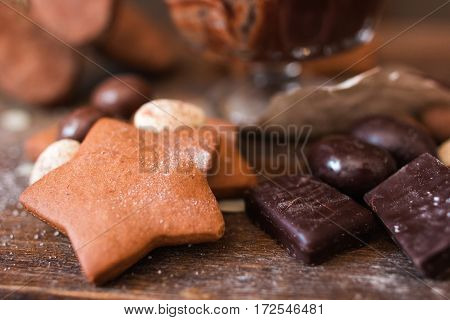 Cookie star with chocolate on wood closeup. Sweets variety on wooden table, confectionery background. Sweet tooth, dessert, pastry, kids paradise concept