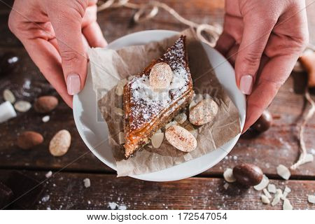 Hands taking saucer with sweet turkish dessert. Baklava with nuts on white plate in baker hands, closeup. Confectionery. pastry, eastern cuisine concept