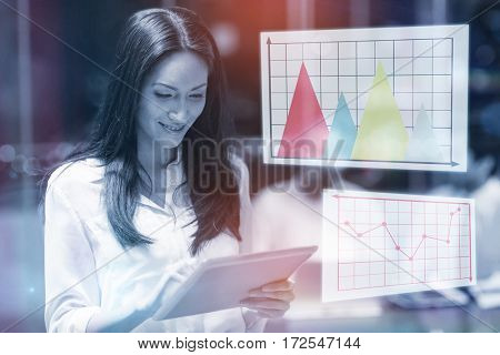 Graph against businesswoman using digital tablet