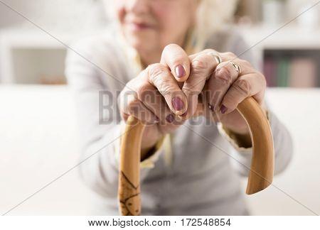 Elderly woman holding on to walking stick