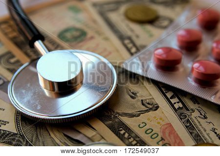 Medical stethoscope pills in blister on a background with money (american dollars and coins). Concept of health care costs.