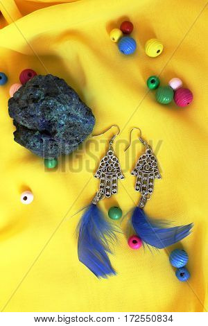 handmade accessories earrings with blue feathers on the yellow background
