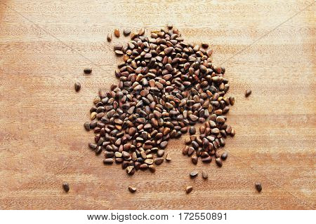 Pine nuts - small seeds of Siberian cedar pine, scattered on a wooden board.