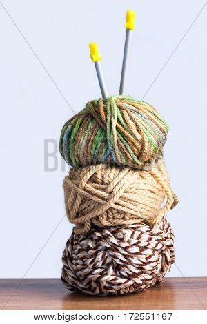 Close Up Of Three Threads For Knitting Green Brown Colors And Spokes On Wooden Board On White Background.