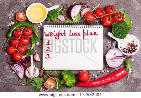 Fresh organic vegetables herbs and spices. Mix salad tomatoes chilli garlic and open blank notebook with plan eating. Weight loss concept. Products for boost metabolism. Cooking healthy food. Top view