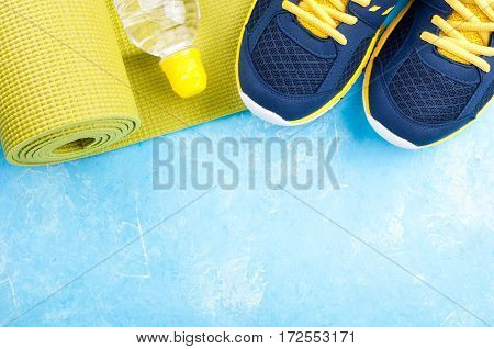 Yoga mat sport shoes and bottle of water on blue background. Concept healthy lifestyle sport and diet. Sport equipment. Copy space