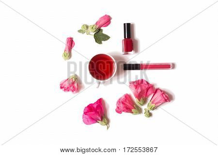 Red flowers nail polish lip gloss are isolated on a white background flat lay top view.