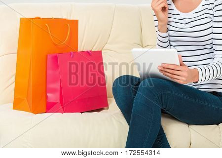 Shopping consumerism concept. Young woman with credit card buying sitting on sofa with paper bags and new clothes