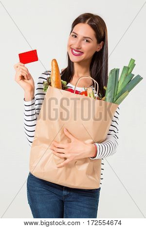 Portrait of beautiful smiling woman holding shopping paper bag with organic fresh food isolated on white background. Girl holding bag of vegetables. Healthy diet