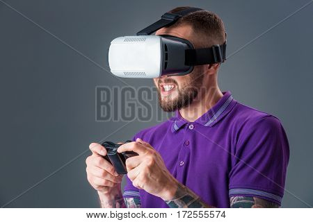 Man in studio wearing virtual reality headset playing game. Man dressed in a purple T-shirt