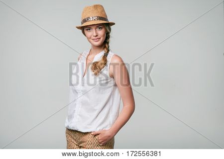 Beautiful smiling woman wearing summer straw fedora hat in carefree stance with hands in pockets looking at camera