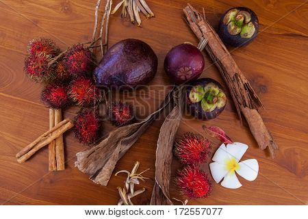 Fresh juicy tropical fruits on wooden table background, top view close-up