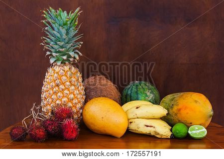 Fresh juicy tropical fruits on wooden table and background, close-up