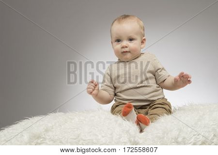 A cute little baby is looking into the camera on the grey backgroud. Studio shot